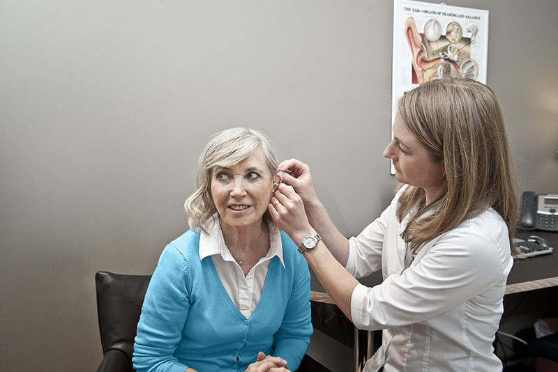 Woman having a hearing aid fitted in a hearing clinic